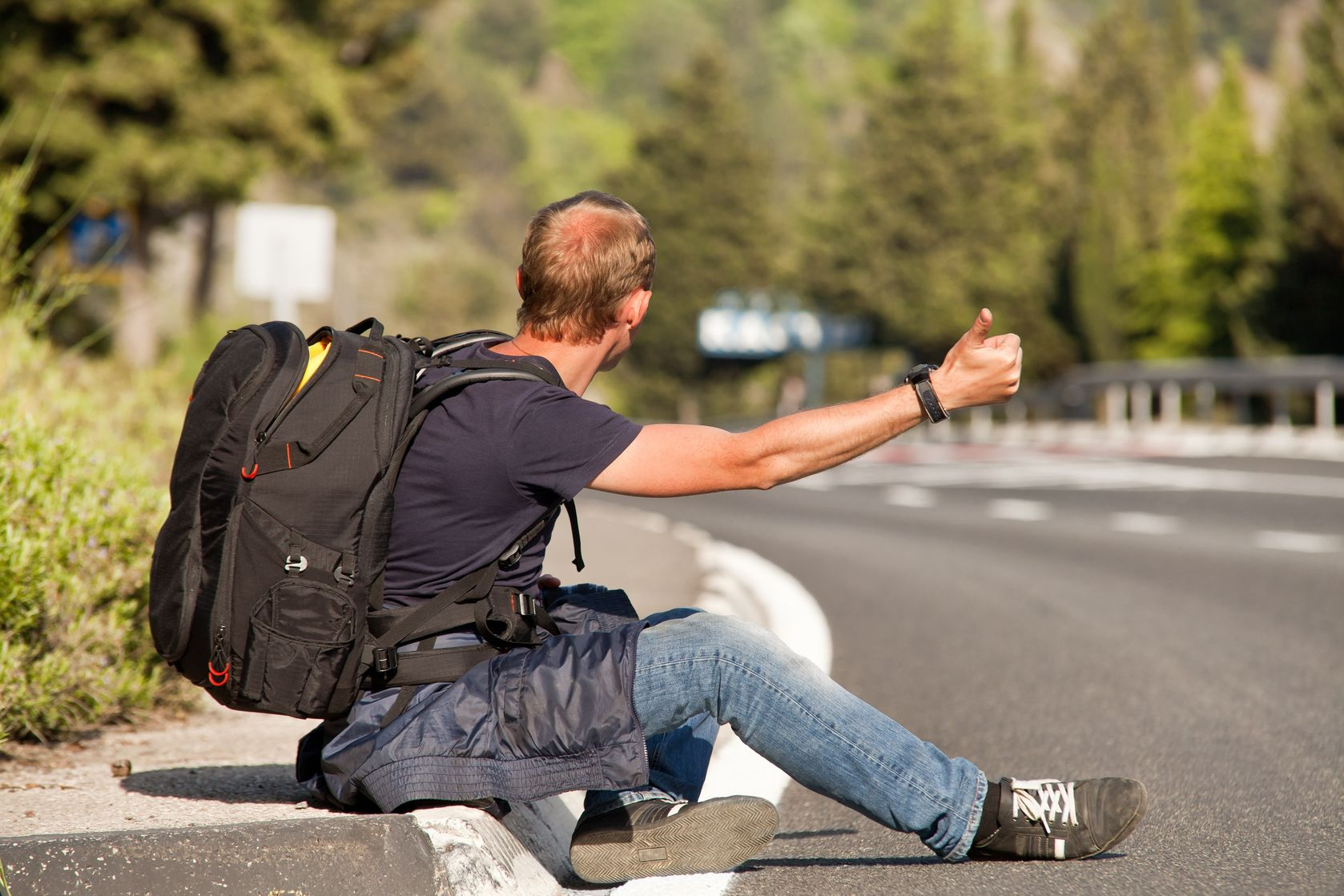 19501550 - hitchhiker traveler sitting on the roadside of the mountain highway